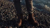 pés : close up shot of a rocky beach, a man stands on the ground in boots, sea waves are beating against the shore, the sun is reflected on the rocks and in the water