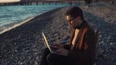 aplicativo : the young programmer prints the text on the keyboard of his laptop, the man is engaged in work during a vacation by the sea, the person is sitting on a rocky beach in an autumn coat