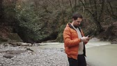 sauvage : Handsome man with beard standing in a forest nearby the river wearing warm clothes. He is texting messages on smartphone. Vidéos Libres De Droits