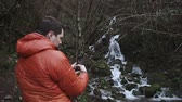 sauvage : Shot from behind of tourist shooting video of a small waterfall in a mountains. Fantastic views of nature.