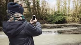 sauvage : Back view of a woman in warm clothes holding smartphone by the river in forest. She is taking pictures and shooting videos. Vidéos Libres De Droits
