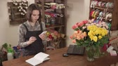 vendedora : Female shop assistant is calculating using mobile phone, in a trading hall of flower shop. She is making notes in a log, notebook and vases with rose in a table Archivo de Video