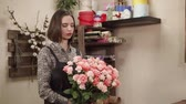 arranjando : Female florist is enjoying view of beautiful armful of fresh roses. She is looking on it and rotating in her hands in a floristical workshop