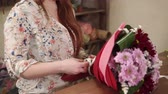 krizantem : Female hands is fastening white ribbon on a floral bunch, close-up. She is making flowers decorations for order in a small floristic shop Stok Video
