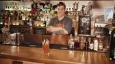 tattoo : Russia Rosa Khutor - February, 2018: the satisfied barman is standing behind the bar and demonstrating a prepared cocktail with tomato juice, this is an alcoholic drink