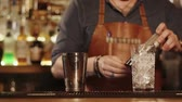 imitation : Close up shot of a working bartender using shakers. He is pouring drink from one to another. Stock Footage