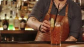 koketní : a close shot at the barmans hands, a man decorates a soft drink with a piece of cucumber and a colored tube, the person finished making a drink for the visitor