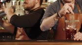 imitation : Two bartenders mixing cocktails in a cafe at the bar. They are using special equipment for mixing. Stock Footage