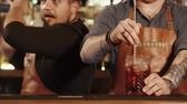 não alcoólico : a close shot at the barmens hands, men prepare cocktails, one of the bar workers stirs a cocktail with a long spoon, the second mixes the ingredients in the shaker