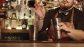 barkeeper : a close shot bar counter behind which is the barman, a man is engaged in the preparation of alcoholic beverages for visitors, he adds rum to the shaker