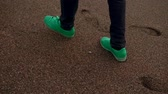 pés : Close up shot of persong in green sneakers walking on beach. Many footprints on a wet sand. Seashore.