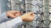 экспонат : Female customer is choosing spectacle frames on racks in shop, Close-up of her hand, she is taking different forms and colors Стоковые видеозаписи