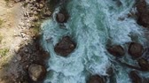 sauvage : a view from above on a fast river stream, water tends to the mouth of the river, inside there are stones that create a flow barrier Vidéos Libres De Droits