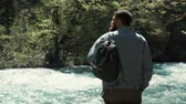 sauvage : Male traveler with backpack is enjoying beautiful landscape in wild forest. He is standing in river shore under sunshine and looking around, experienced hiker
