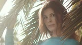 sensual : portrait of a young and beautiful model who poses near a green palm tree in a park, a lady looks happy and pacified, her face has a natural make-up Vídeos