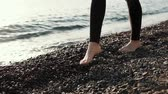 pés : a close shot at the womans legs, the lady with thin ogami strolls along the stony beach barefoot, she steps on small pebbles , the waves beat on the shore Vídeos