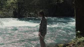 sensual : Shot from behind of a brunette woman spending day by the flowing river in the forest. Beautiful day on the nature. Fast stream.