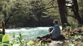 sensual : Handsome man in a jeans jacket is sitting at rivers bank alone and relaxing. Spending day in the forest. Fast flowing river. Vídeos