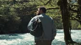 sensual : Shot from behind of male tourist with a backpack standing in a forest by the river. Handsome man in a jeans jacket spending day in nature.