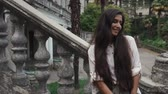 mehendi : a young woman with dark long hair is standing near the stairs with a stone frame, the lady has tattooed mehendi on her hands, she is looking away while in the park Stock Footage