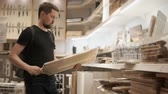 l air : Bearded man is taking in hand large wooden chopping board in a store. He is weighing it, waving in air and thinking about buying Vidéos Libres De Droits