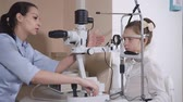 보정 : Side view shot of a female ophthalmologist working with young girl. She is using slit lamp for examining her eyes. 무비클립