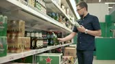 browar : Russia Togliatti - June 2018: Male visitor of a supermarket is a holding in hands glass bottle and metal can with beer. He is reading inscription on labels in a store