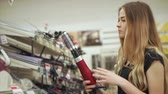 comparar : Female customer wants to buy new curling iron for her hairstyle. Woman checks the quality of a new iron. Shopping for a beauty tools.