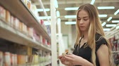 incandescente : Alone young woman is holding incandescent lamp in hands in a hall of supermarket. She is getting it from paper box and checking a spiral Stock Footage