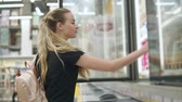 изобилие : Beautiful young woman buying frozen yogurt in a supermarket. Customer takes yogurt from a fridge in store. Sweet snack. Consumer goods. Стоковые видеозаписи