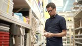 householder : Male shopper is choosing plastic containers for storage in a hypermarket. He is opening, twirling in hands and collating sizes Stock Footage