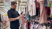 baby store : Casual father choosing new dresses and outfits for his child, shopping alone. Man in glasses buying kids clothes in mall.