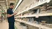консервы : Casual brunet guy in glasses standing by the fridge in supermarket and choosing canned seafood. Buying canned fish, herring.