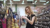 puderdose : Young woman customer is examining and inspecting small folding umbrella in a store. She is standing in trading area of hypermarket alone