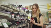 negócio : Charming blonde girl choosing new curling iron in store, beautiful hairstyle. Young blonde model buying tools for curly hairs.