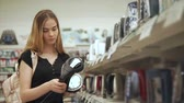 bule : Housewife is examining electric tea kettle in a hall of store. She is opening and closing cover of exhibition sample Stock Footage