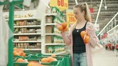 мандарин : Slim girl is shopping fruits in a hypermarket. She is taking different packs with oranges and choosing one