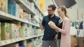 baby store : Man and woman standing in aisle with baby food and choosing baby formula for kid. Wide selection of baby nutritions. Excited new parents.