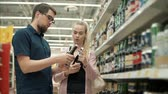 spouses : Man and woman are deciding which brand of beer to choose. Guy and girl are holding glass bottles in hands, discussing covers Stock Footage