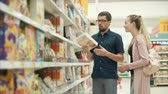 aveia : Man and woman are debating a cereal for cooking in a grocery department of supermarket. Husband is offering product and woman is deciding