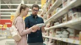 aveia : Male is debating with his wife which kind of cookies to buy. He is taking pack from shelf and showing to his woman, looking together Vídeos