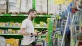 price cut : Male customer of hypermarket is choosing tools in department. He is taking hatchet, spinning in hands and hanging back on shelf Stock Footage