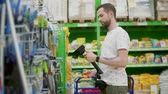 důvěryhodný : Grown man with beard choosing new tools, holding small axe with sharp blade. Man checks quality and weight. Hardware store. Dostupné videozáznamy