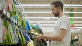 à prova d'água : Man is groping rubber gloves for gardening works in a shop. He is touching and checking materials of goods Stock Footage