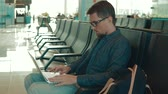registrar : Portrait of a man in eyeglasses using laptop in airport terminal area alone. Man waiting for flight in a hall, tourist travels by plane. Vídeos