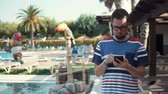 à beira da piscina : Adult man with glasses is strolling in resort area near pool in sunny day. He is checking messages and news in his mobile phone
