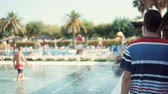 à beira da piscina : Rear view of a man walking by the pool in a resort, vacation in summer, holidays. Man enjoying summer days by the hotel pool in a resort area.