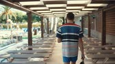 à beira da piscina : Shot from behind of a man walking between lounges with backpack in a hotel resort on vacation, tropics. Male tourist hanging out by the pool. Vídeos