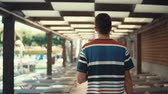à beira da piscina : View from behind of a casual guy by the pool looking for lounge chair to lie. Man traveling in summer, tourist abroad in a resort, vacation.
