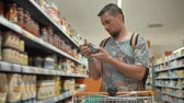 kochen : Man choosing ketchup sauce for cooking at home, shelves with food in a store. Customer with a shopping cart in a grocery store, buying groceries. Stock Footage